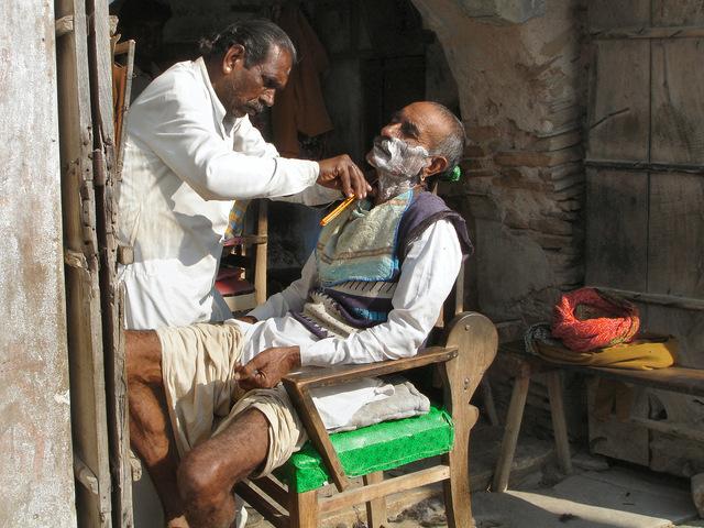 holič v Indickém městě se zákazníkem